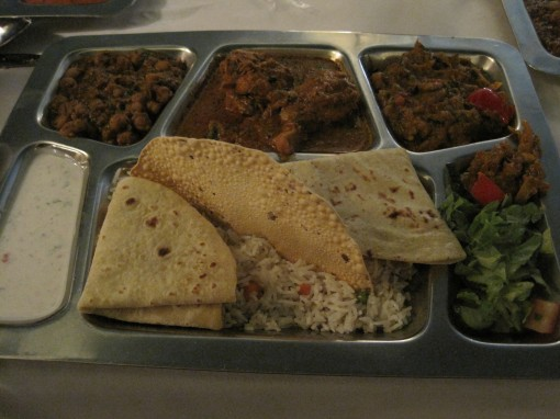 The thali is delivered in a metal tray.