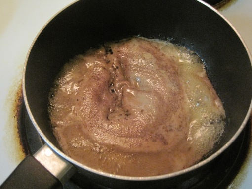 Solid forming in the lamb juices as they heat. The brown layer on top is later strained  off the juices.